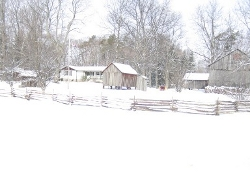 guest house in winter showing rail fence and outbuildings